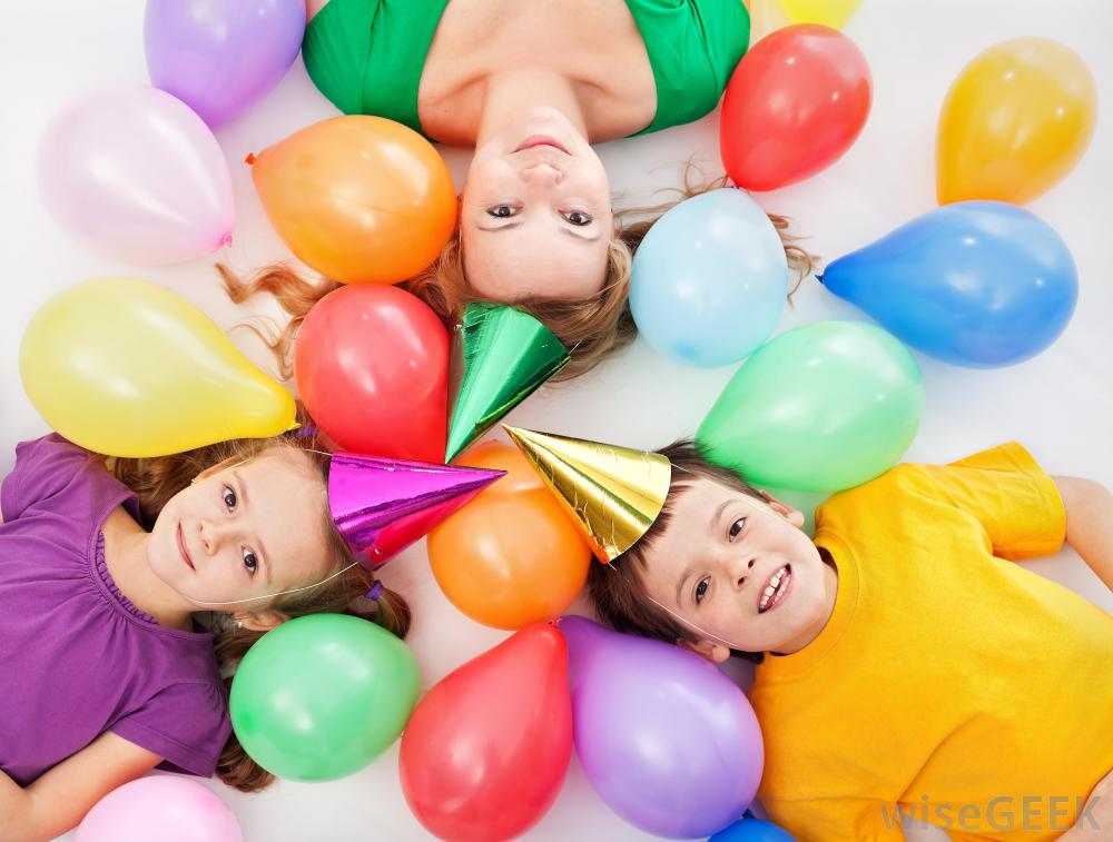 children and adult wearing birthday hats near balloons